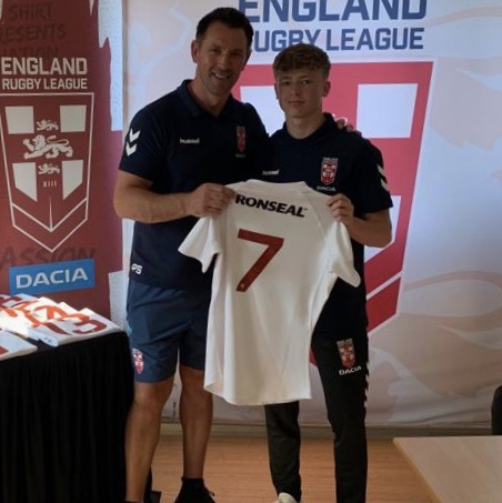 Logan Astley is presented with his England shirt by former Great Britain international Paul Sculthorpe.
